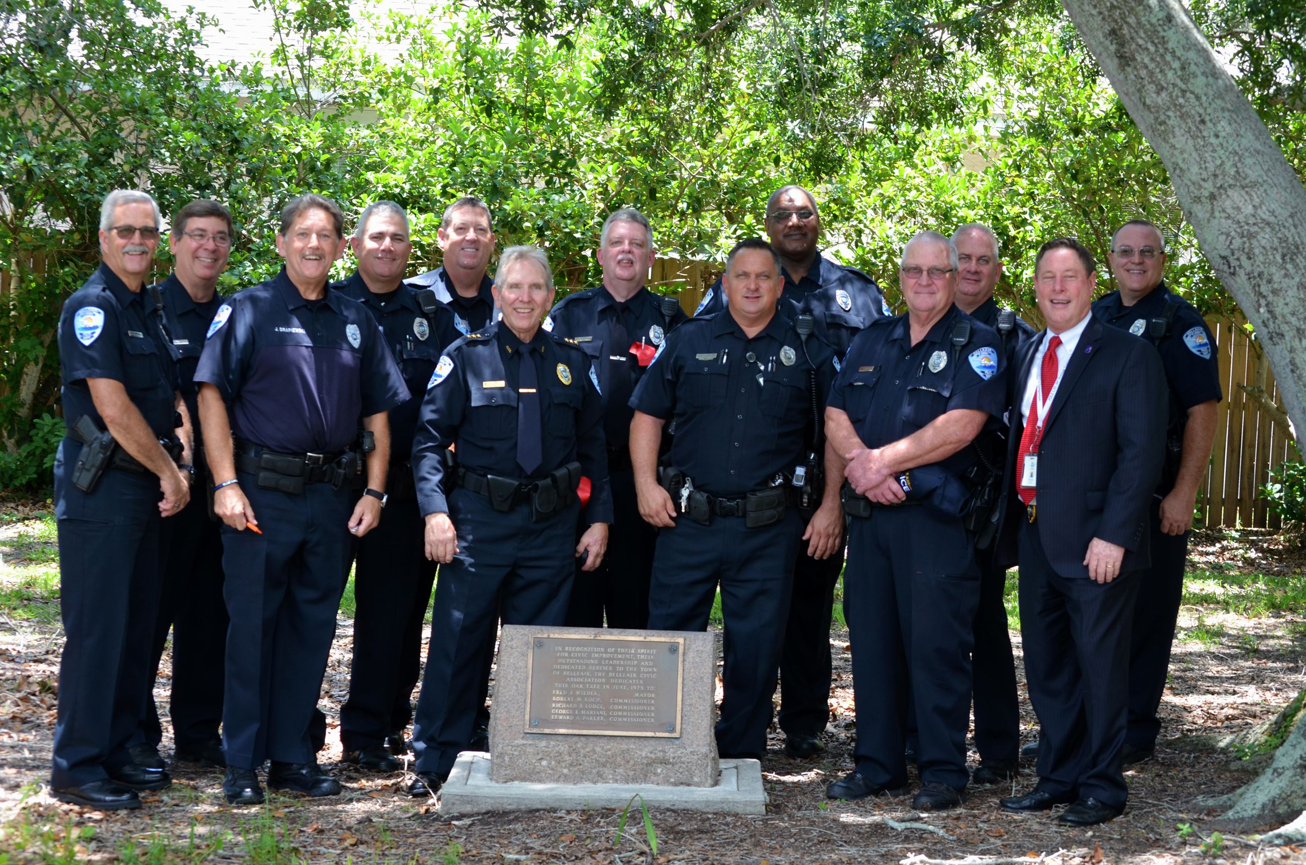 A group of Belleair Police officers in uniform smile in Tackett Park before construction begins.
