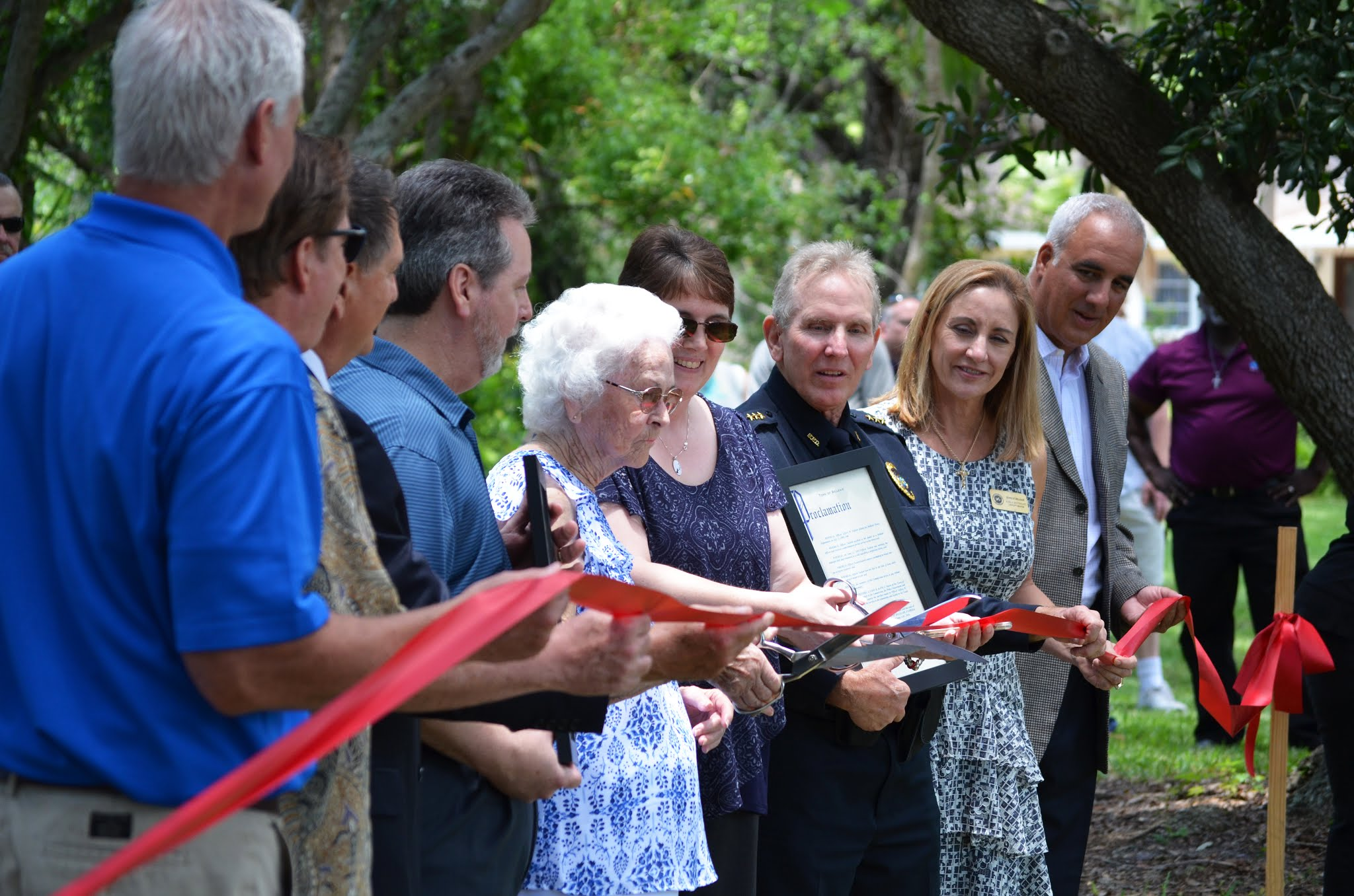 Town staff, Commissioners, and family of Officer Tackett cut a ribbon at Jeffery W. Tackett Park