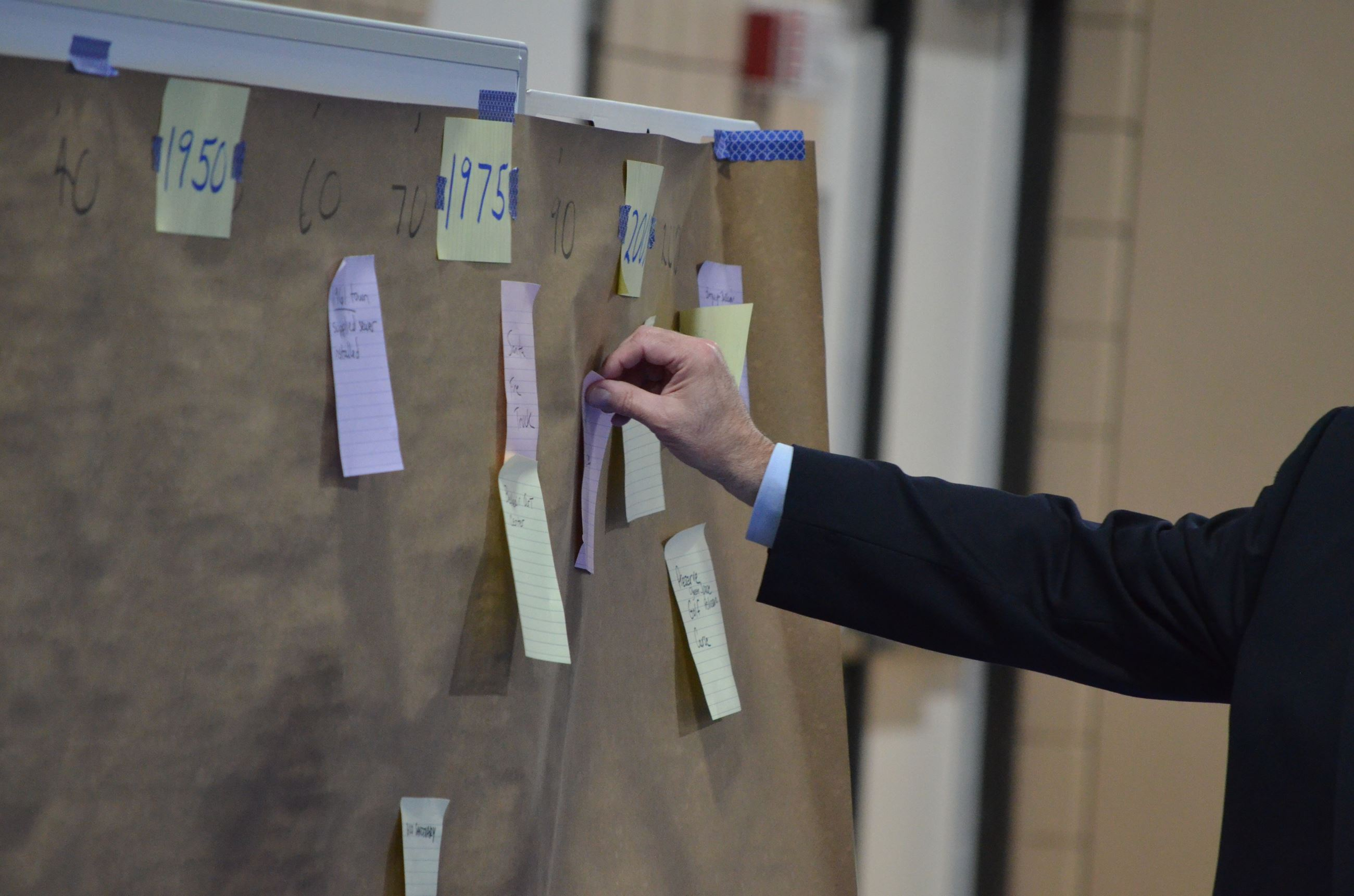 A man places a sticky note onto an interactive timeline of Belleair's history