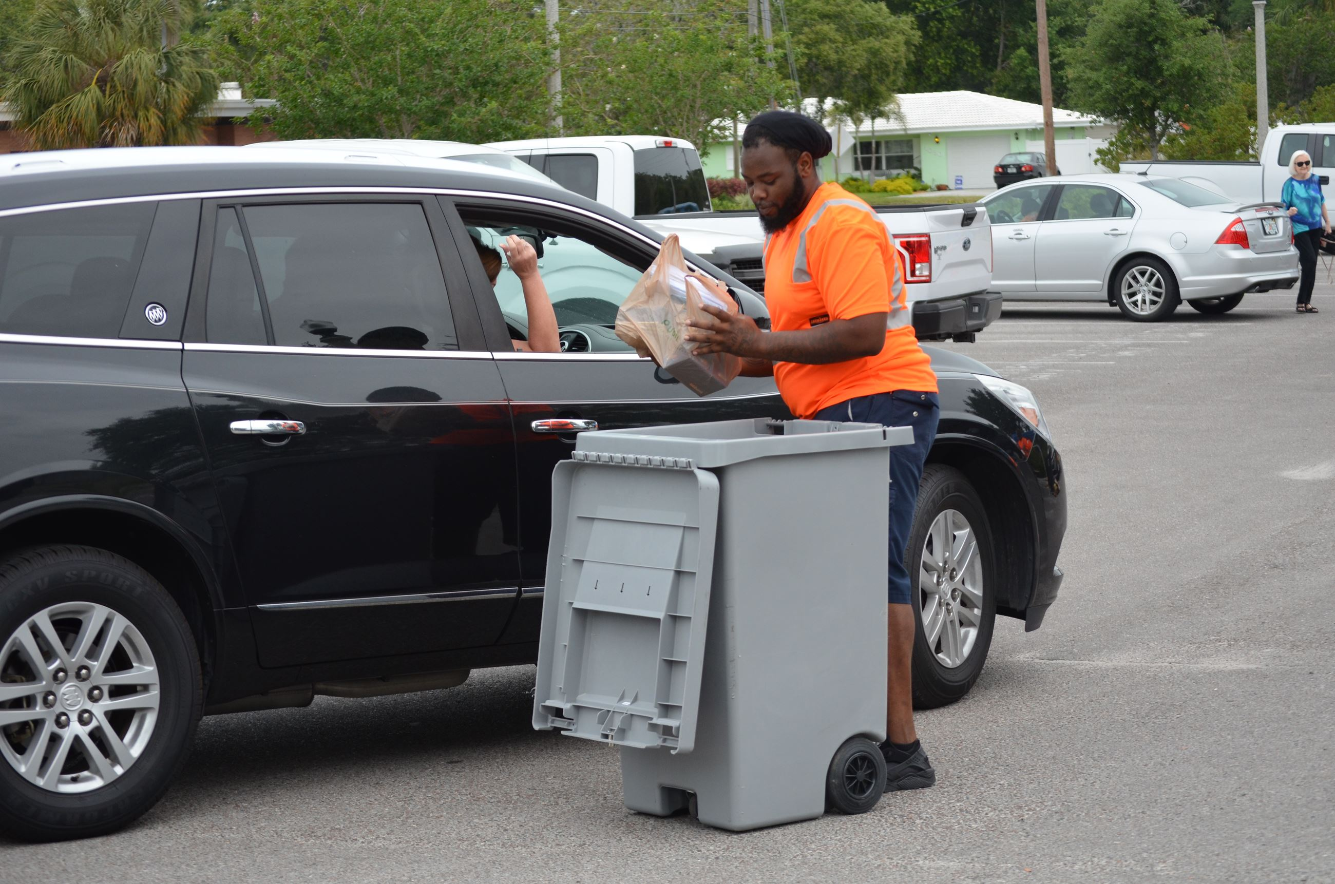 Image of staff collecting papers from a car at a previous shredding event.