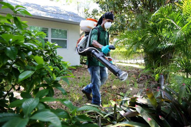 Pinellas County Mosquito Control employee wearing a mask and using a machine to spray for mosquitos