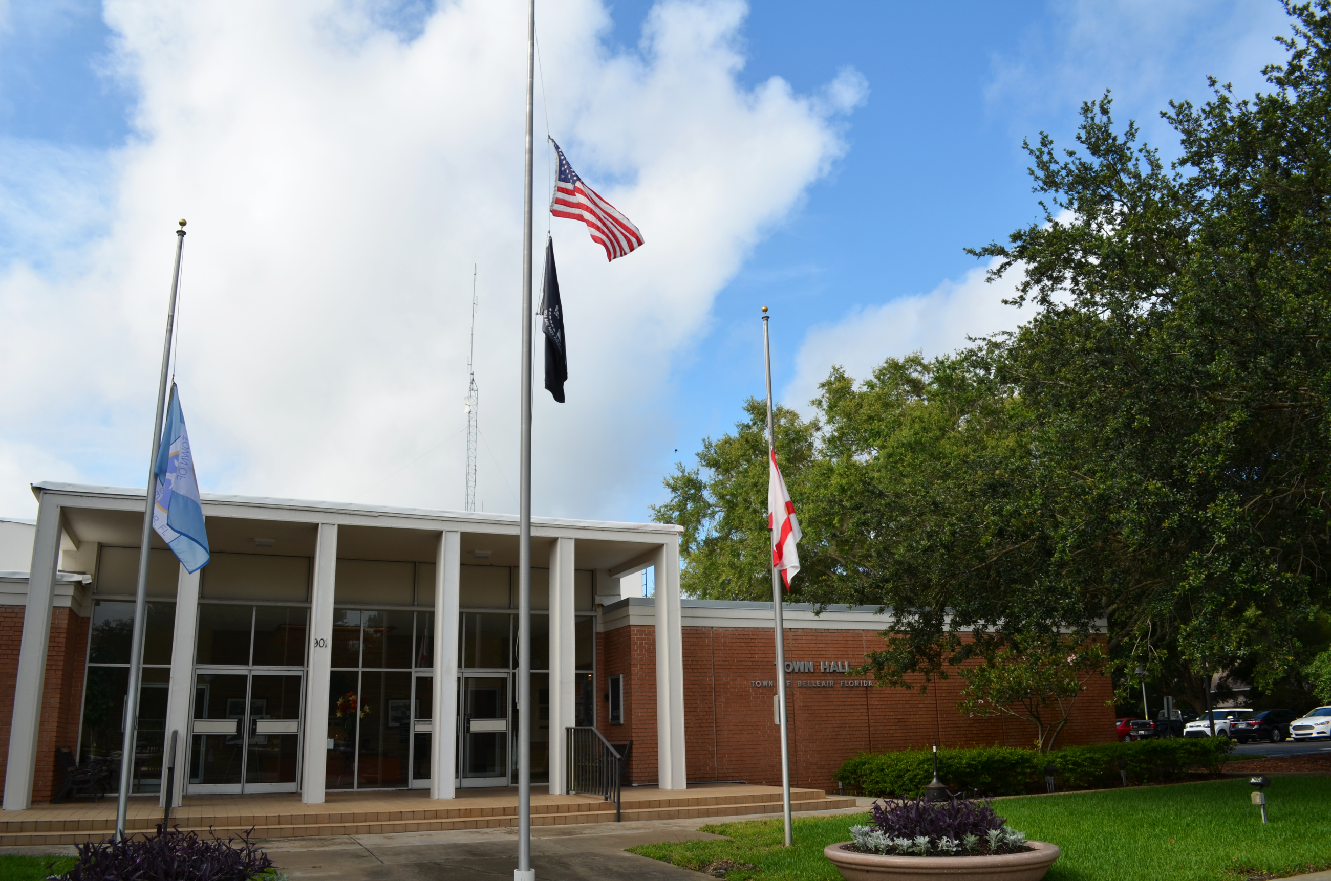The front of Belleair's Town Hall building with flags at half staff.