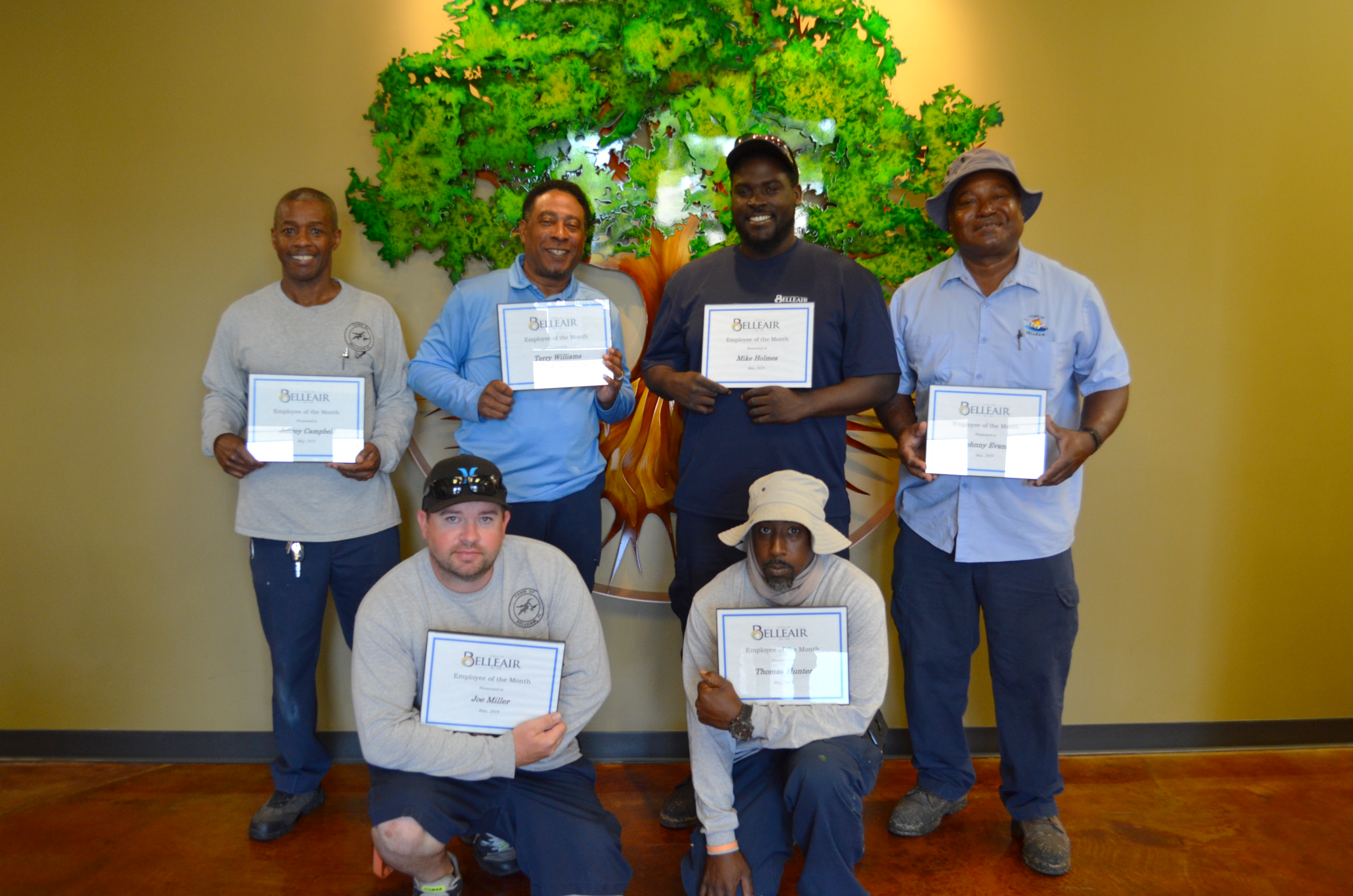 Six members of the water department smile with their employee of the month certificates for May, 201