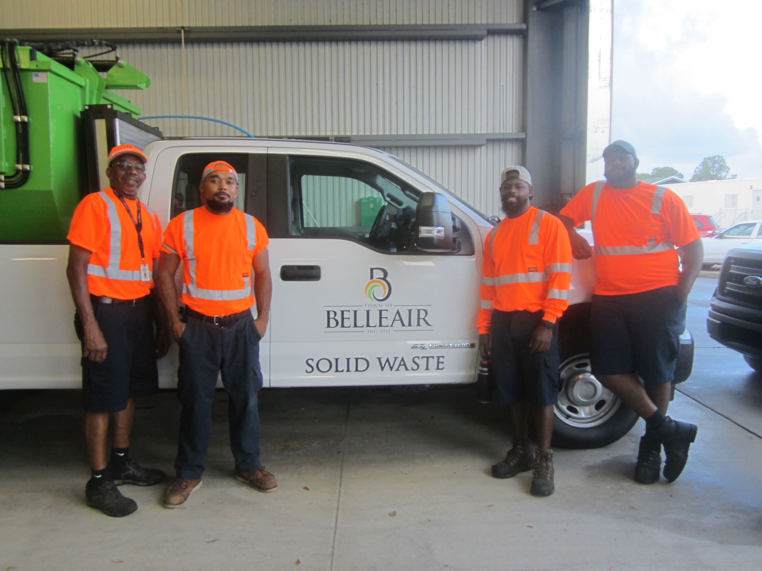 Four members of Belleair&#39s Solid Waste Department smile in front of the Town&#39s satellite picku