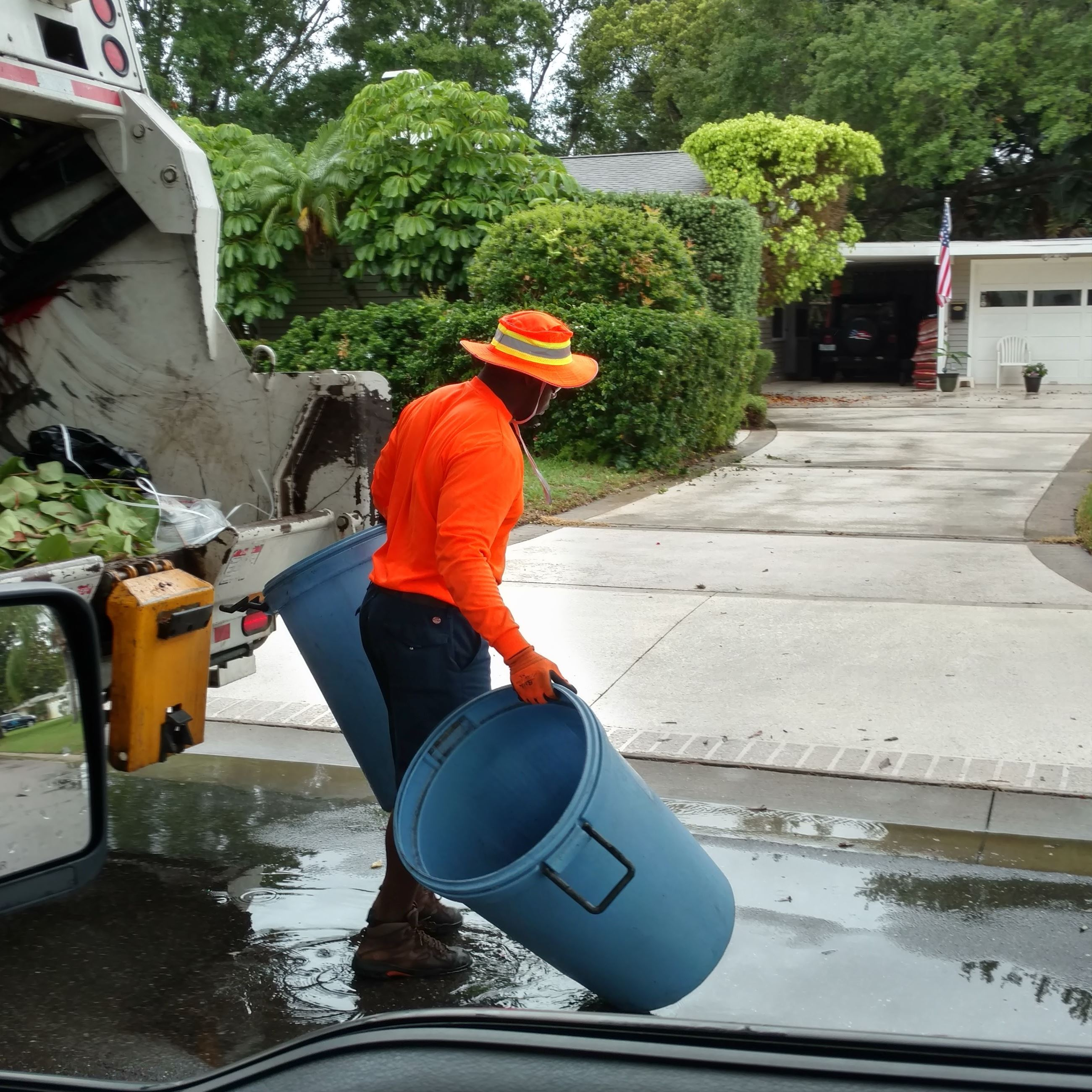 A solid waste employee empties trash into a truck on a rainy day in Belleair
