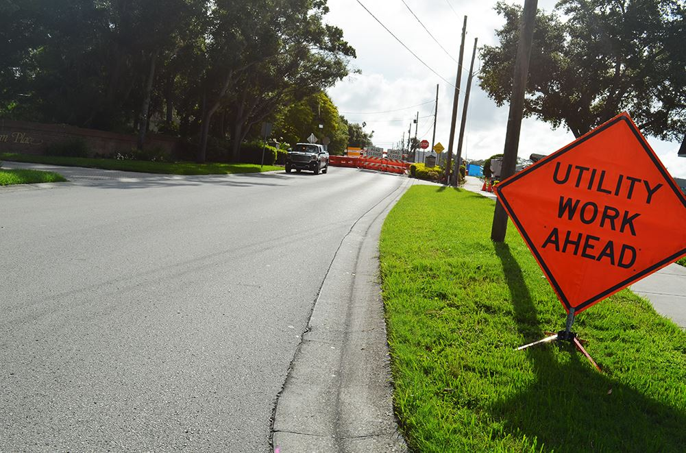 "An orange sign on Poinsettia Road before the Pinellas Trail reads ""Utility Work Ahead"" - cones"
