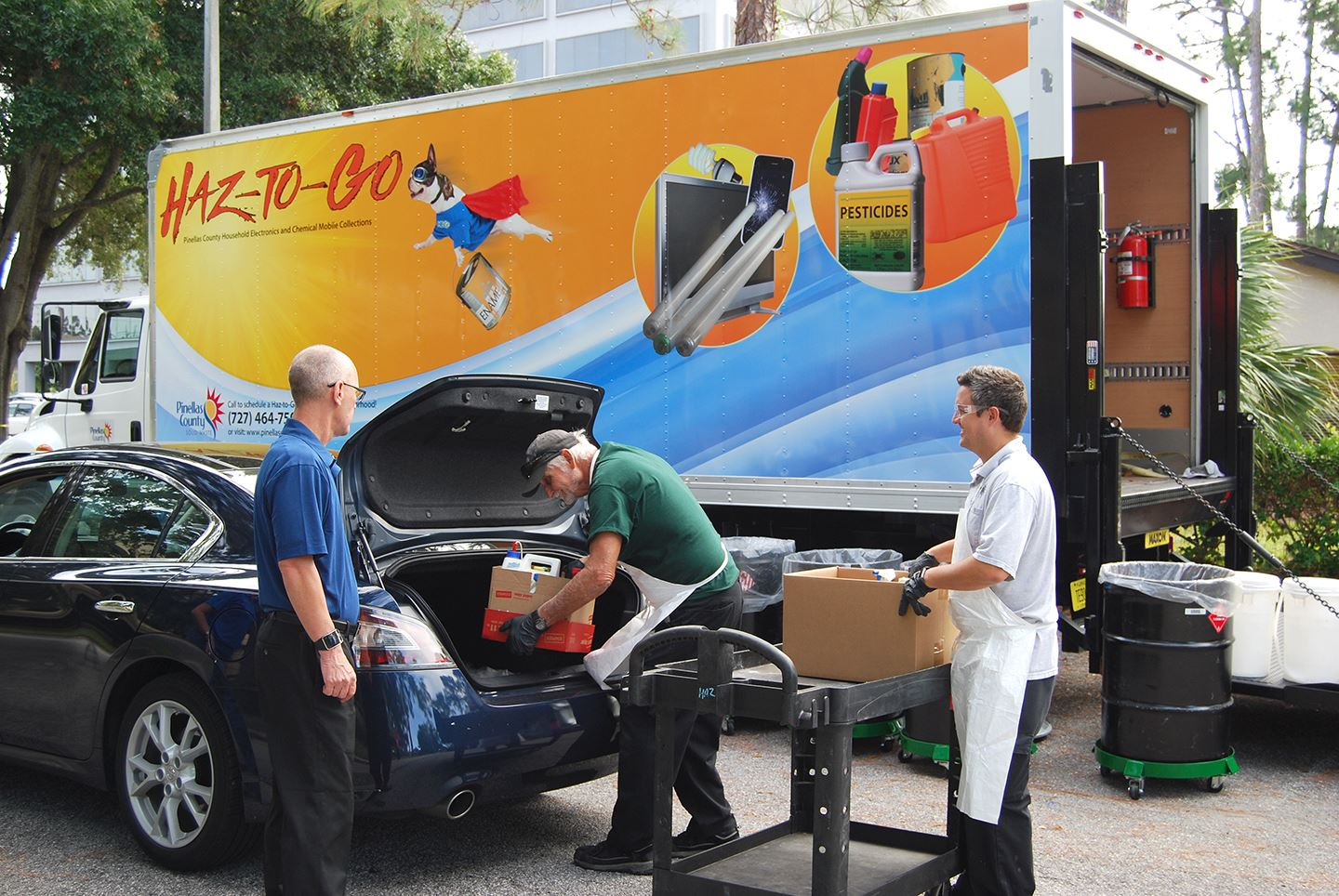 Two Pinellas County employees remove chemicals from the truck of a customer's car