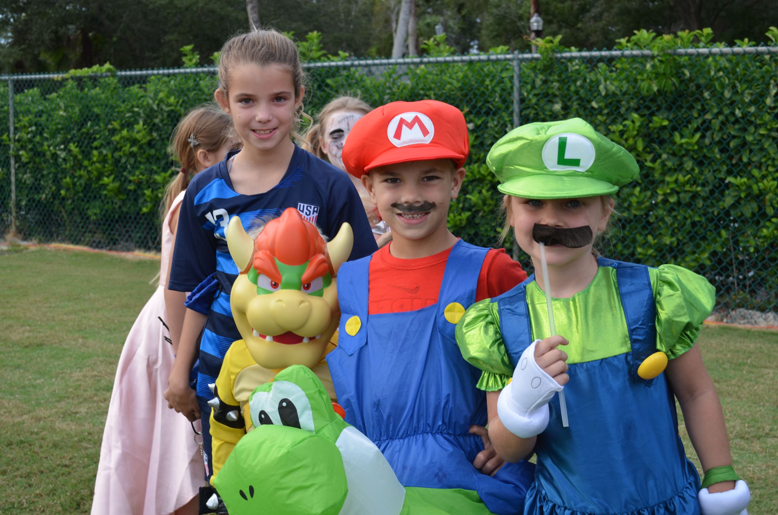 Three children dressed as characters from Nintendo&#39s Mario pose for a photo before the costume co