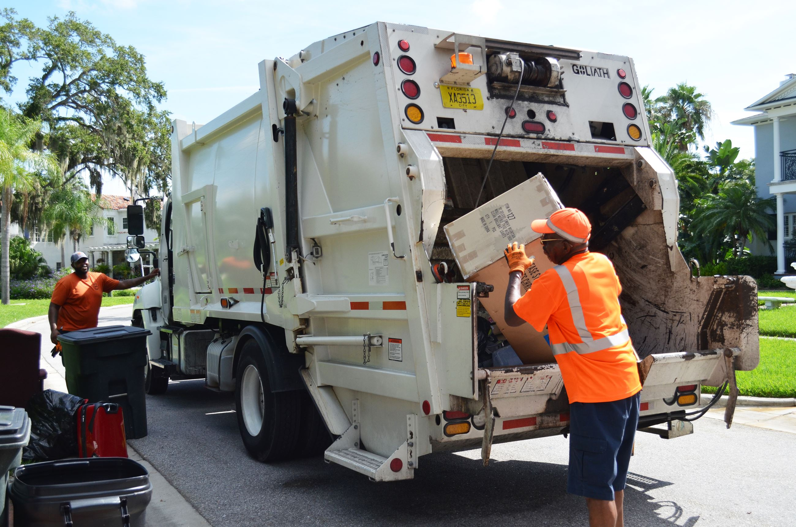 A solid waste employee dumps a trash bin into the back of a garbage truck.