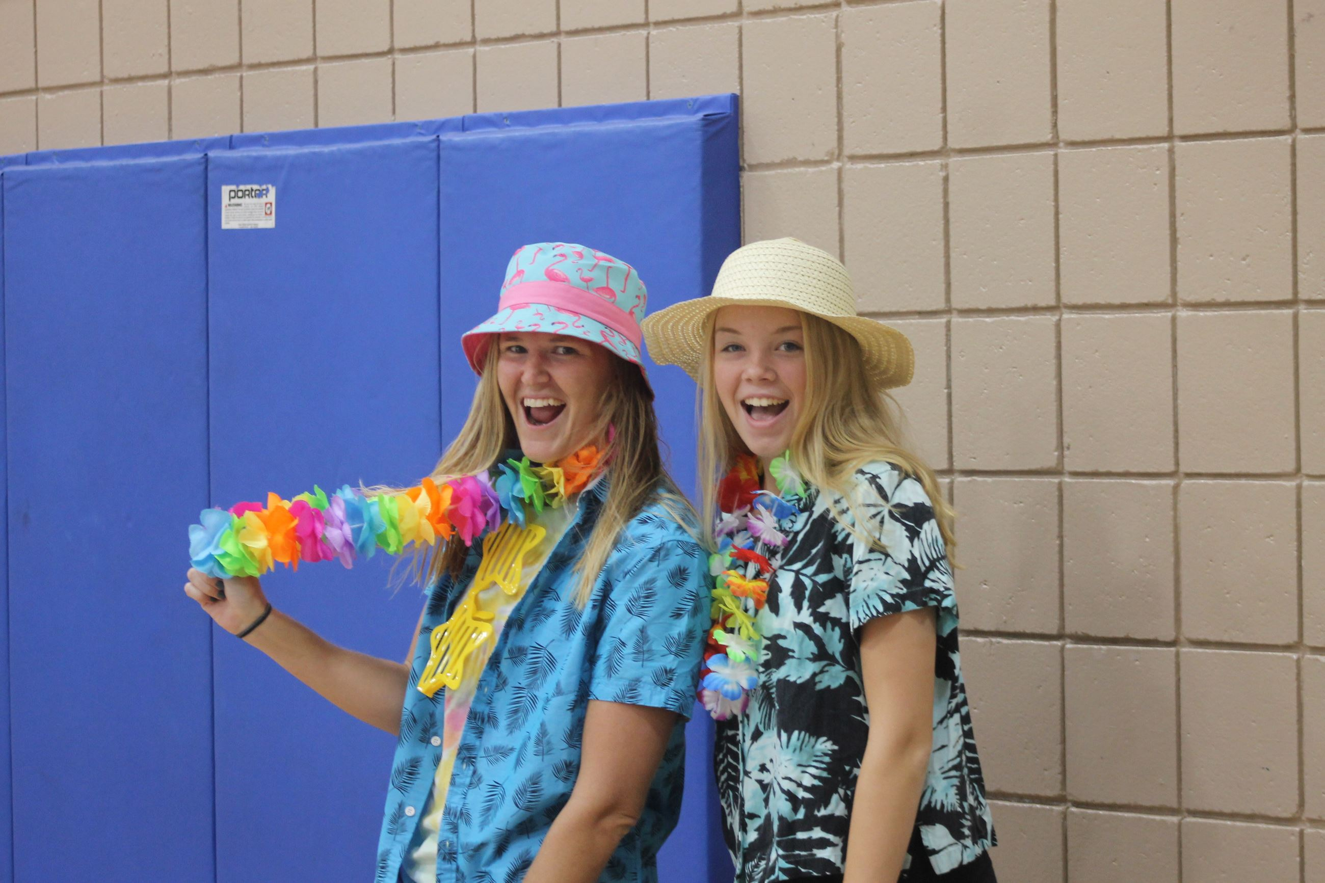 Two recreation employees wear tacky tourist gear at a themed day at summer camp