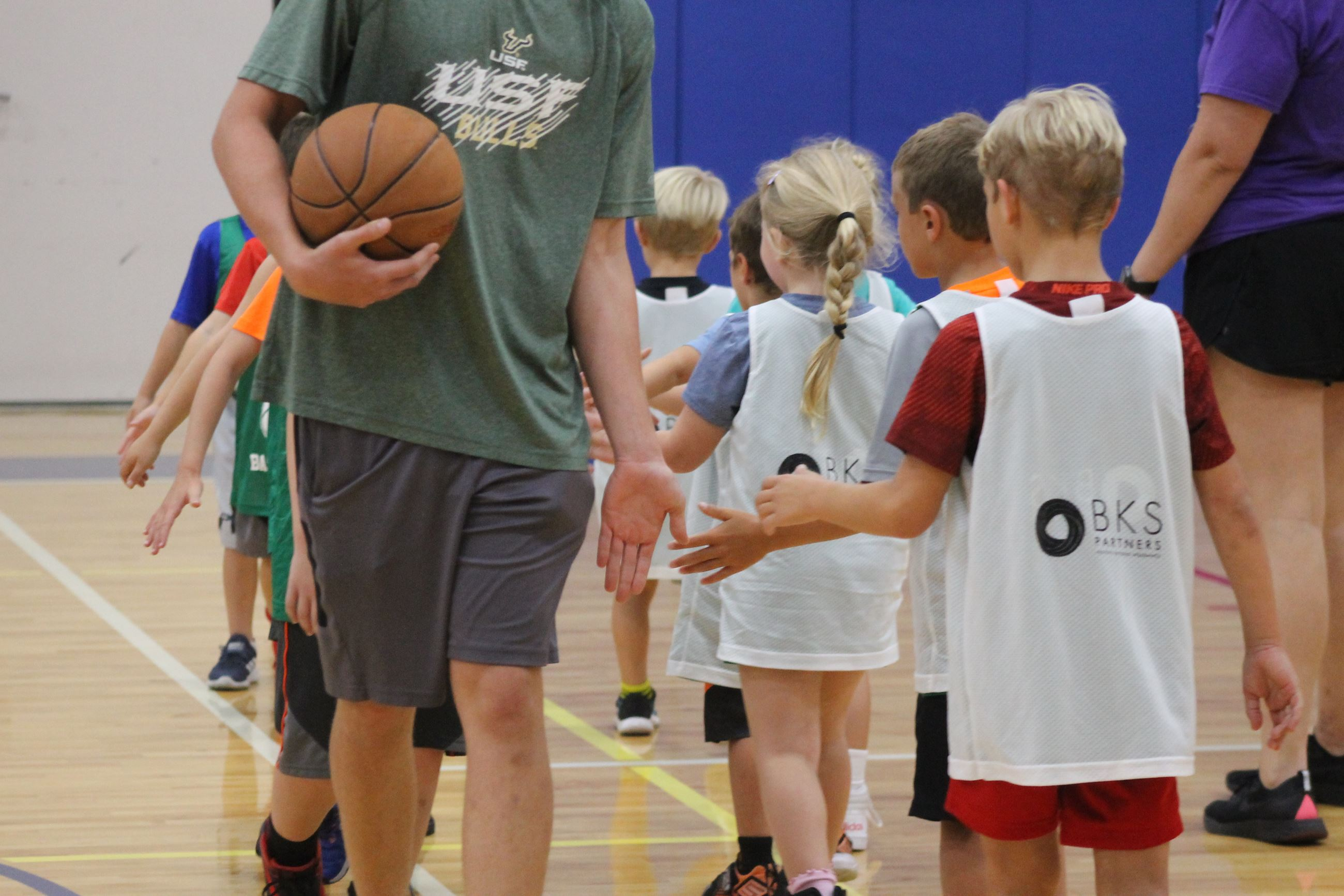 Children and coaches are lined up, high fiving after a basketball game