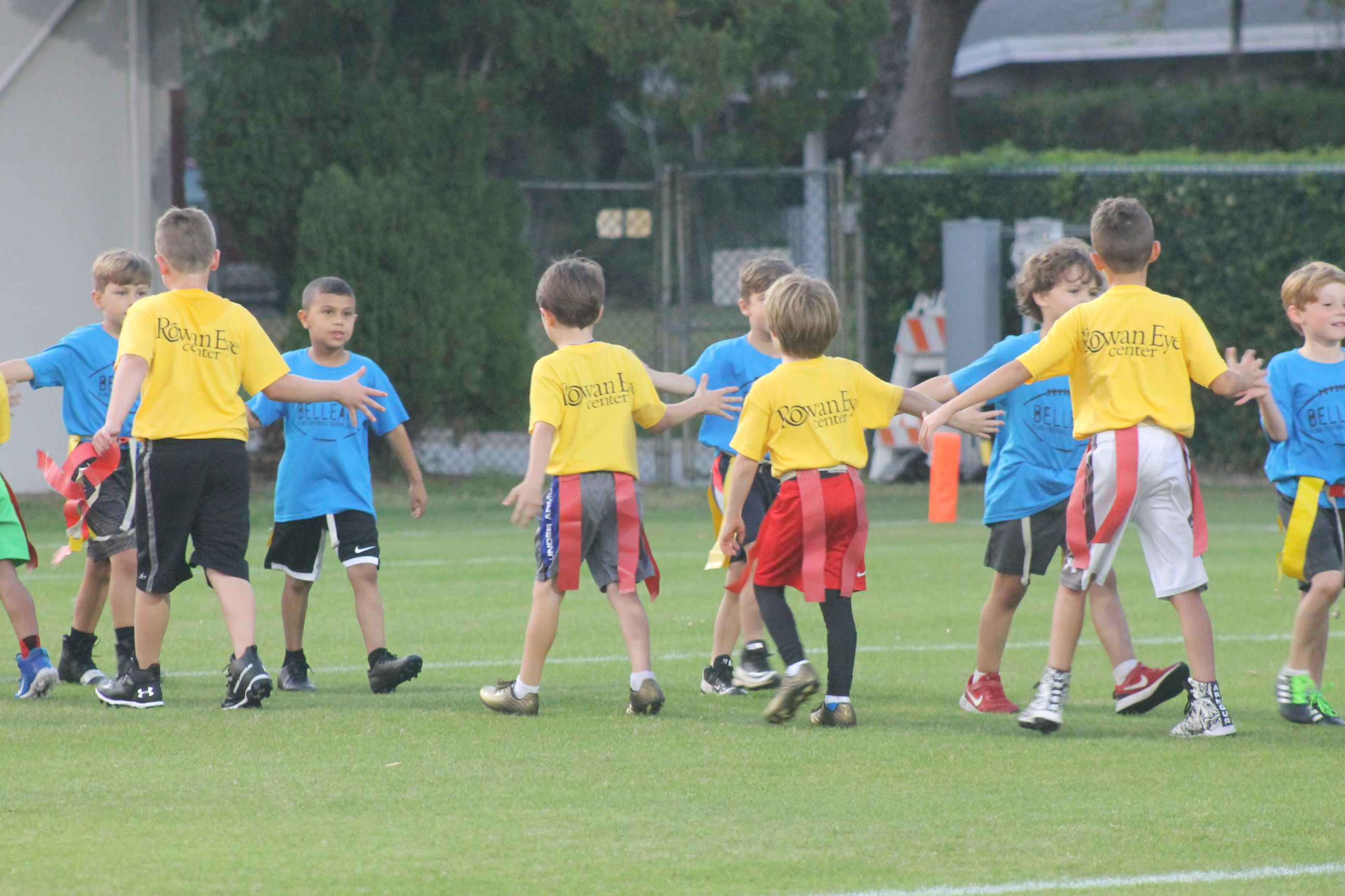 Children on a field are lined up, high fiving after a flag football game