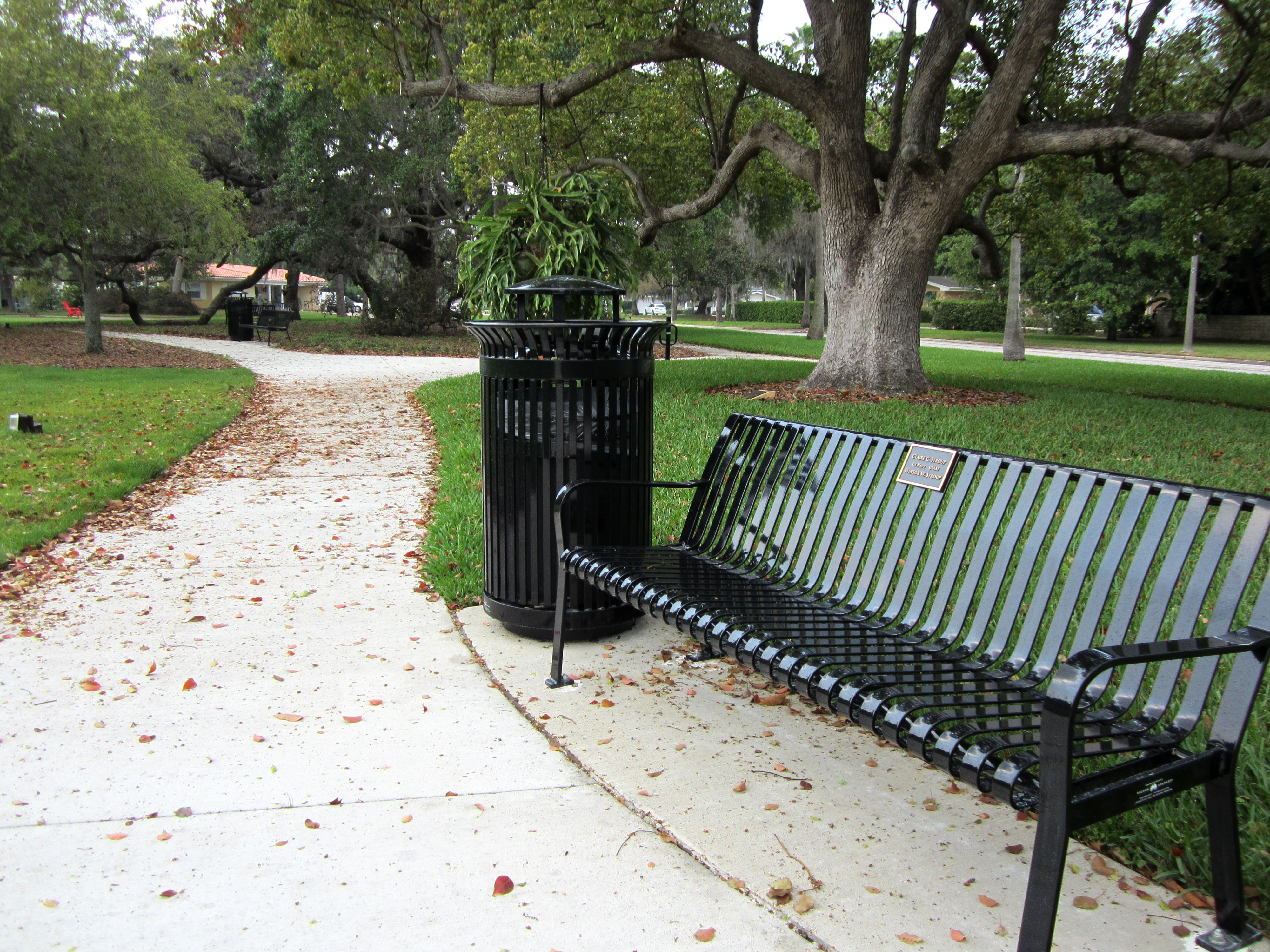 A black bench and trash can in Hunter Memorial Park that sit along a sidewalk path