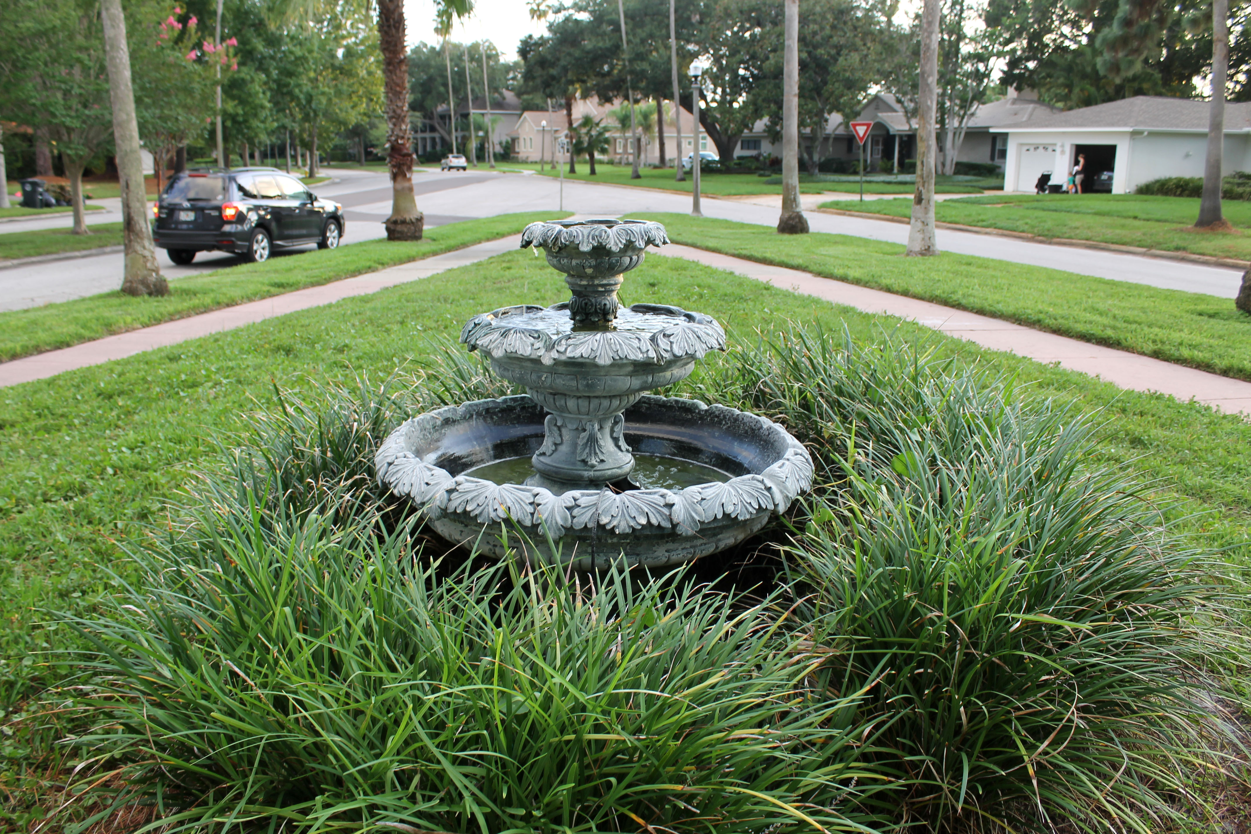 A three-tiered fountain in Pine Park with plants around it