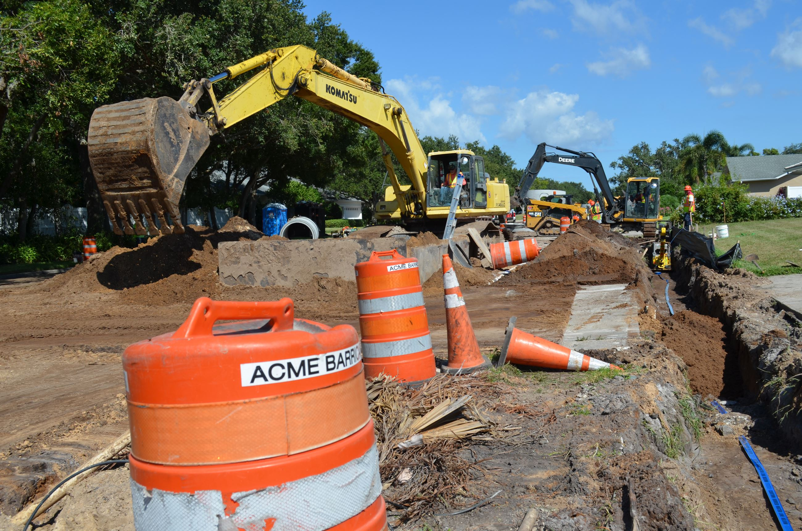 Two backhoes are being operated to place drainage pipes beneath Ponce de Leon Boulevard