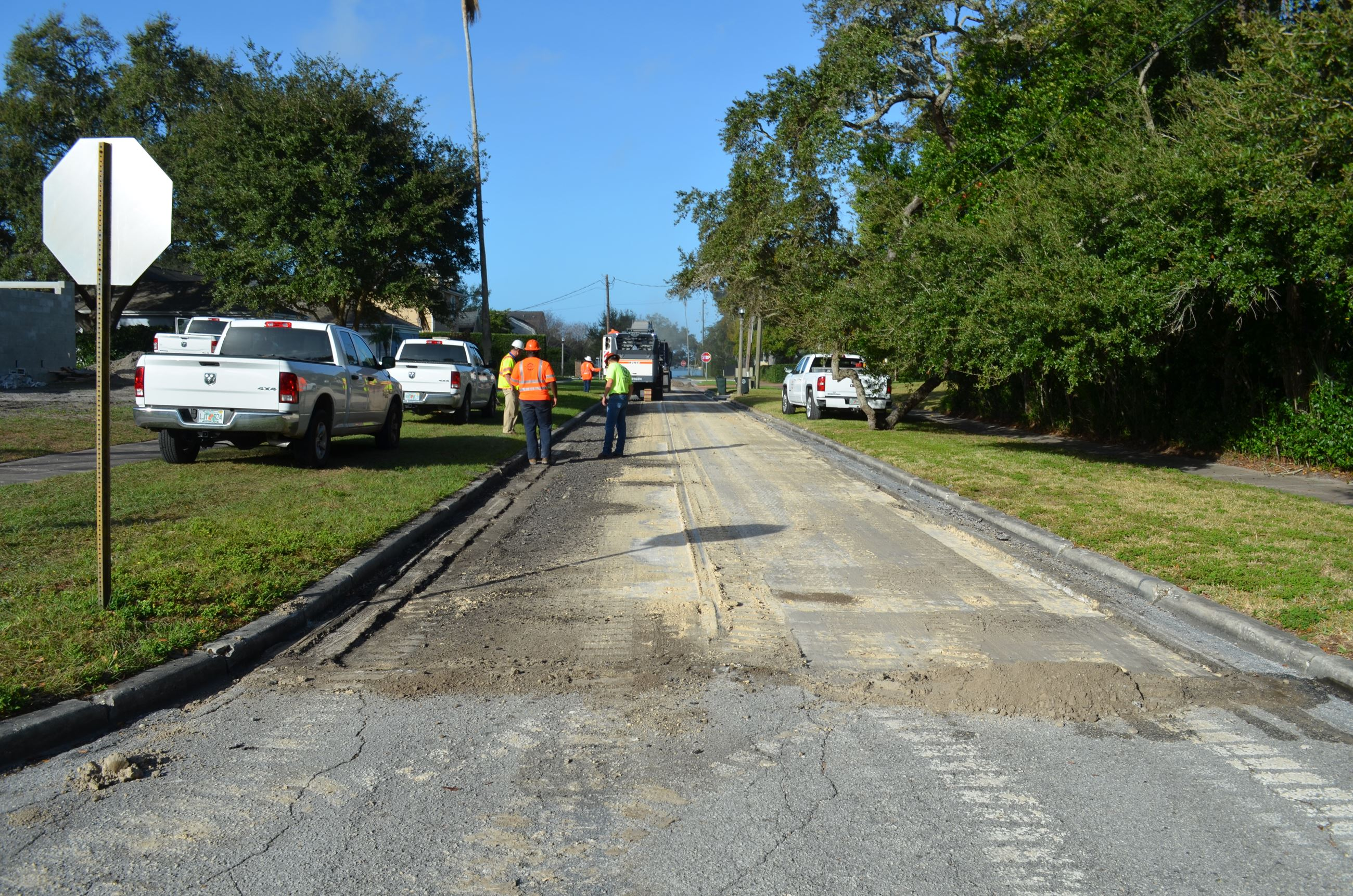 Contractors use a large machine to mill off a layer of asphalt from Orlando Road. Material left behi