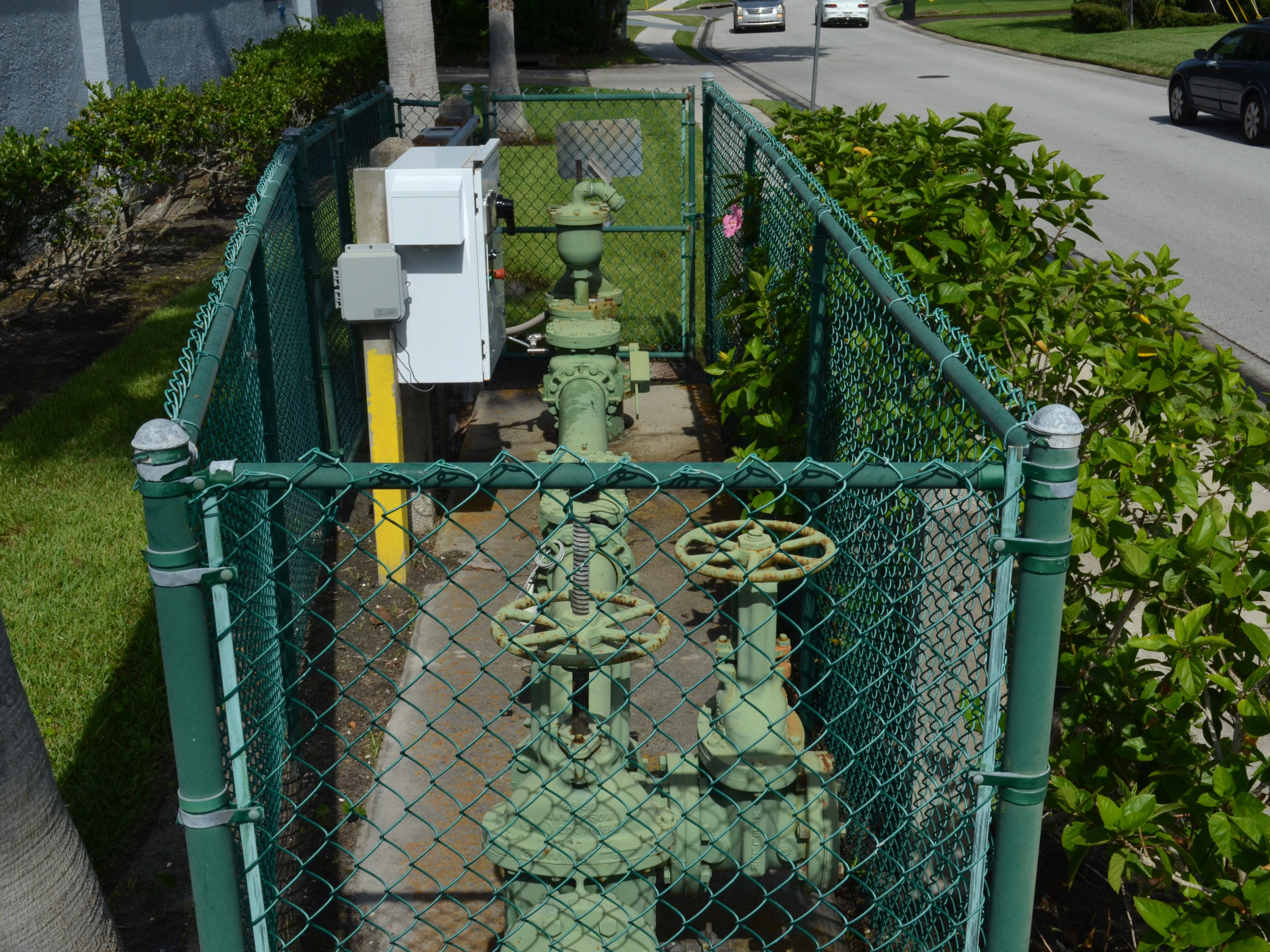 A green raw water well pump inside of a fenced area.