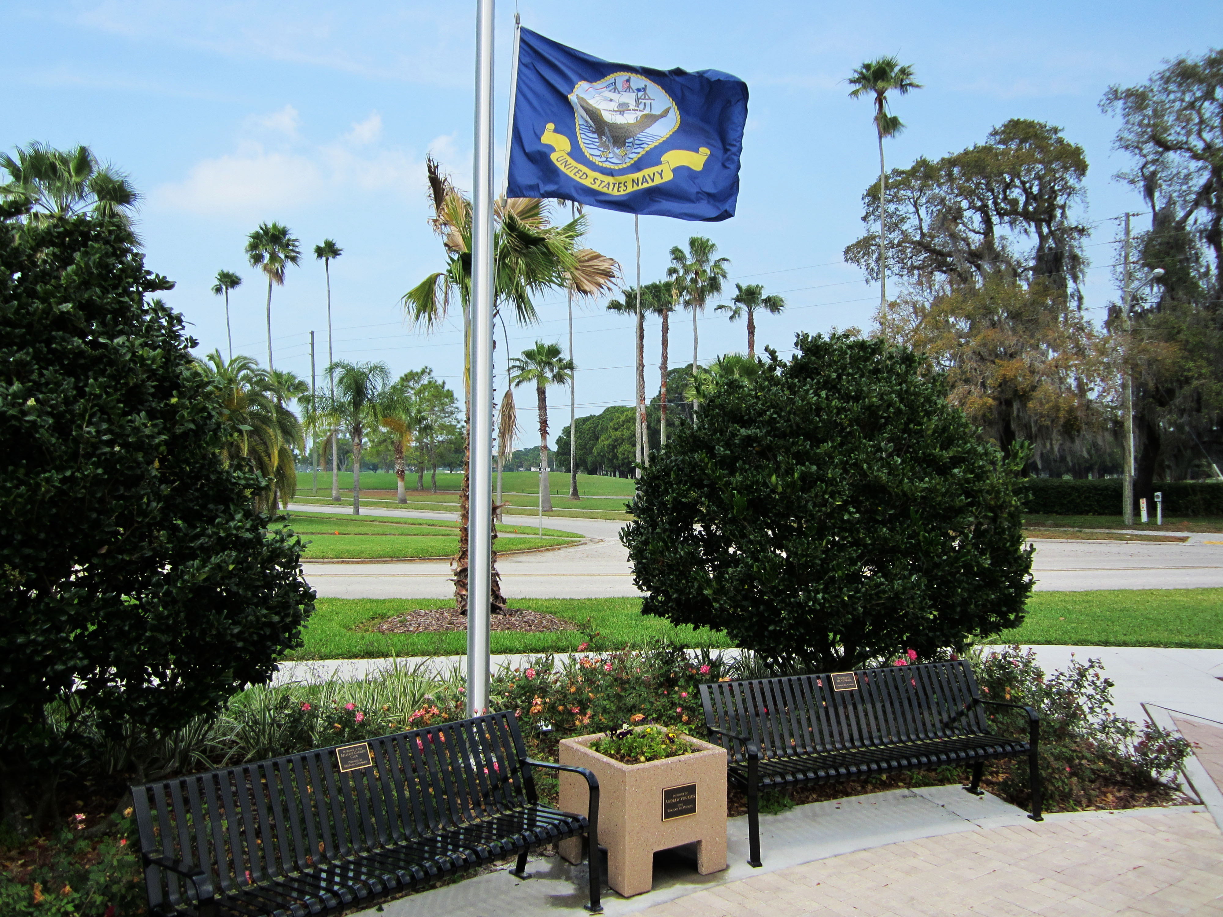A flag for the United States Navy flies a half staff next to two benches in Hunter Memorial Park