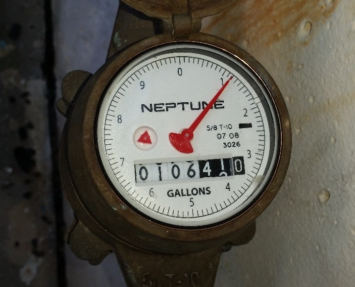 A water meter typical of one found in Belleair with a white face and a red needle.