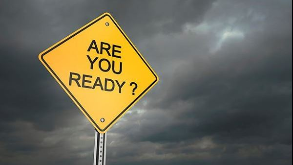 "A yellow sign that reads ""ARE YOU READY?"" surrounded by a dark storm"