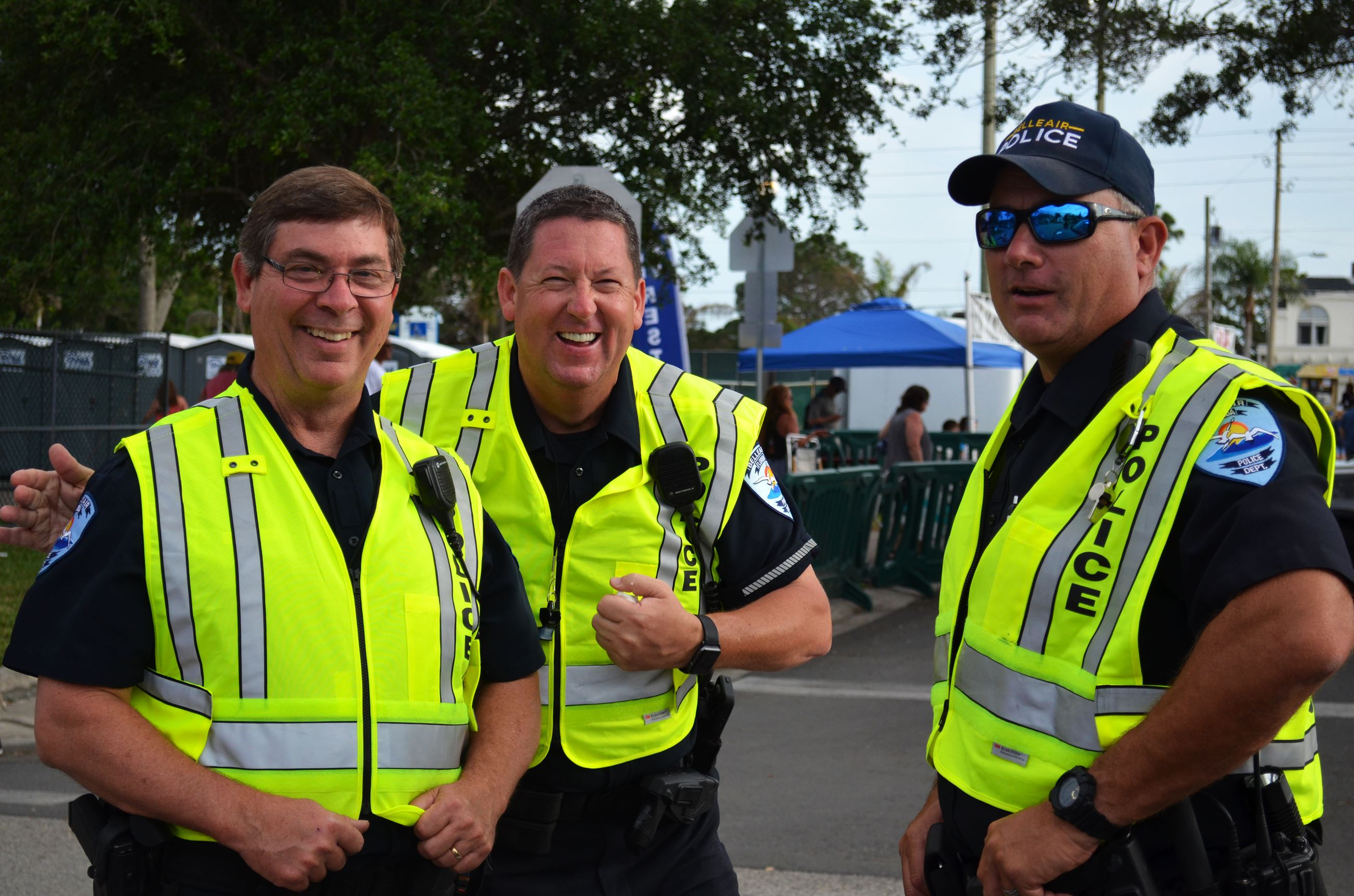 Belleair Police Officers in safety vest smile while working at a Town concert.