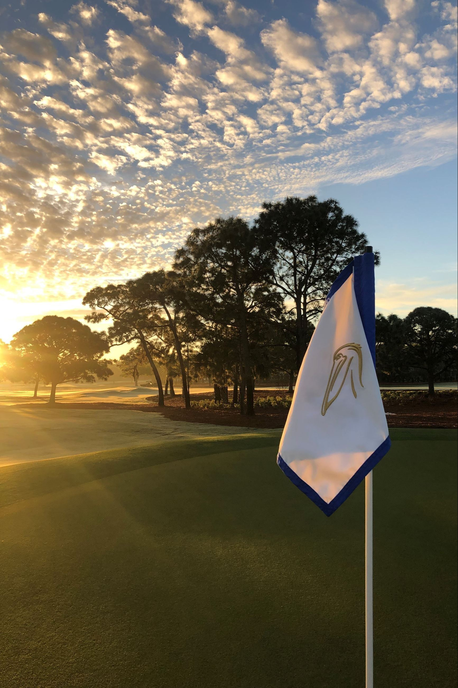 A flag with the Pelican Golf Club logo stands on the course with the sun setting in the background.