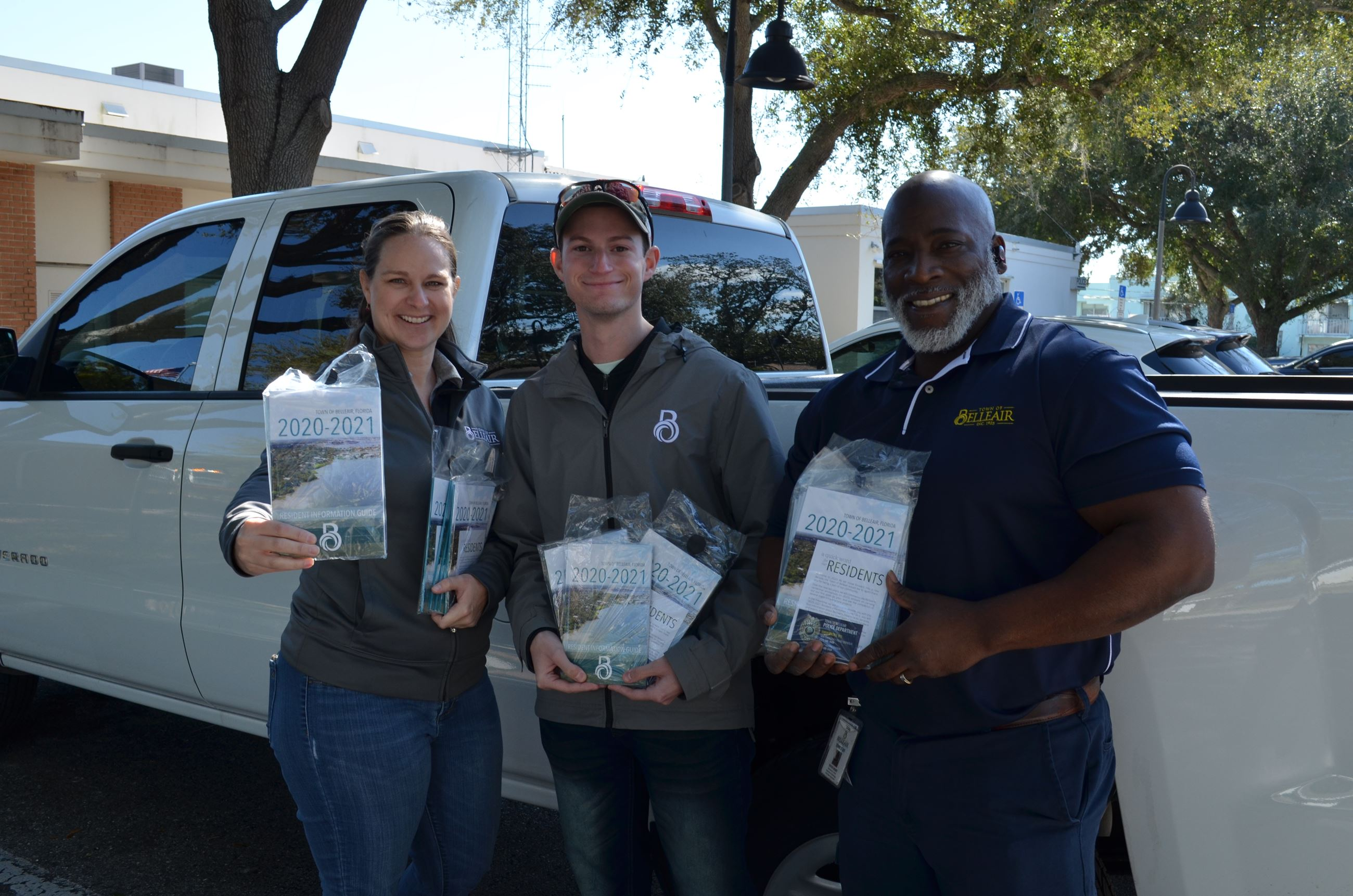 Three town employees hold copies of the resident information guide prior to delivery.