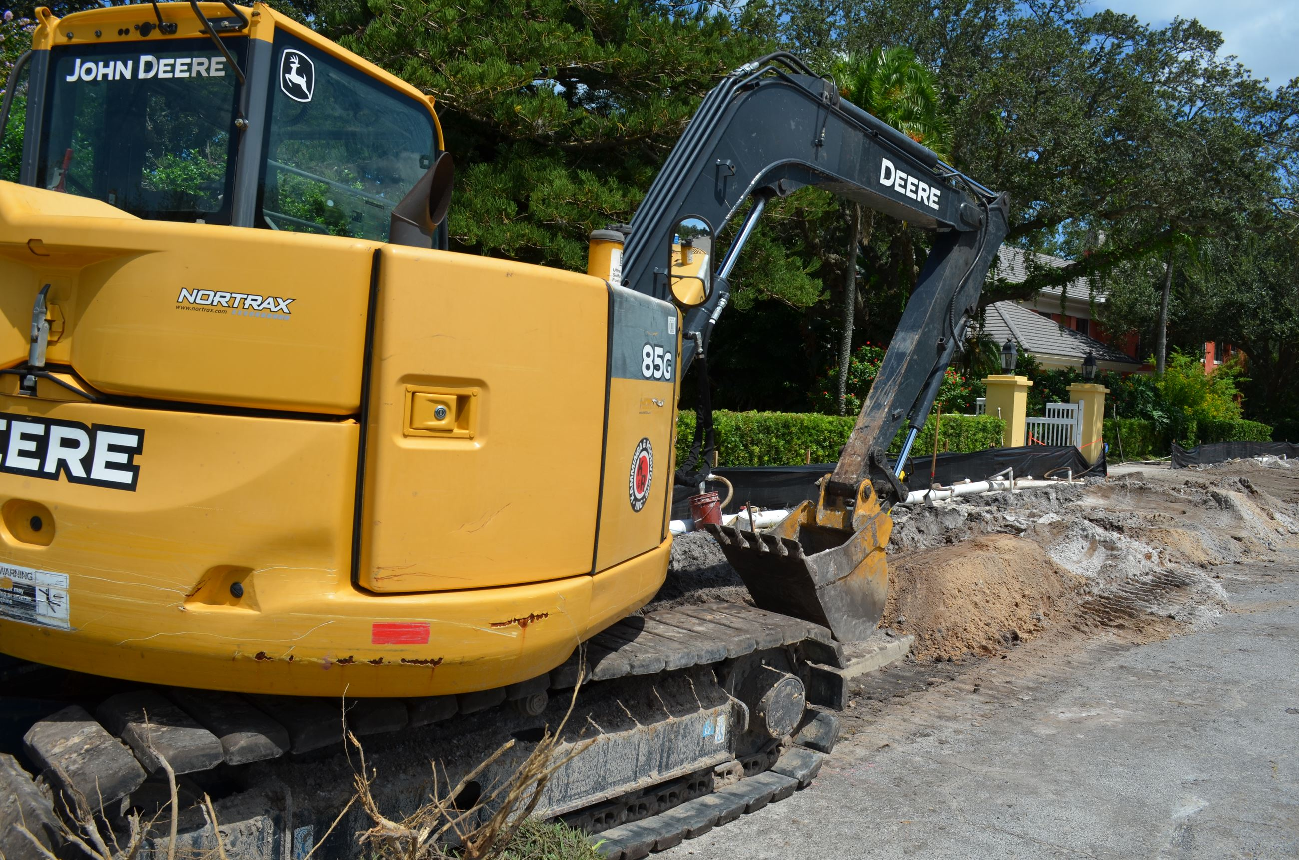 A yellow backhoe sitting on the side of Palmetto Road near an area where dirt has been dug up.